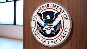 a black sign with white text on a wooden surface: DHS IG won't investigate after watchdog said Wolf, Cuccinelli appointments violated law
