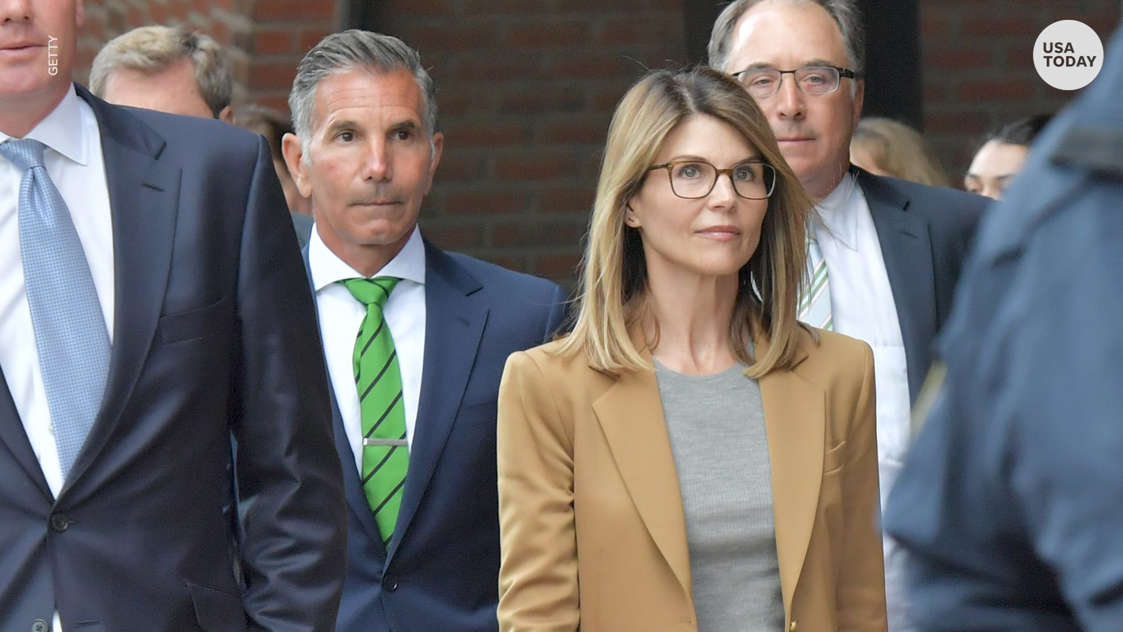 Lori Loughlin et al. standing next to a man wearing a suit and tie: Lori Loughlin and her husband Mossimo Giannulli have agreed to plead guilty to conspiracy charges.