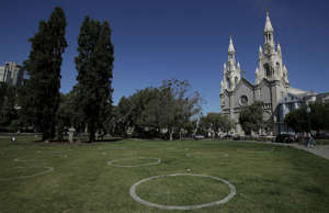 Circles designed to encourage social distancing are shown at Washington Square park in front of Saints Peter and Paul Church in San Francisco. The closure of many churches nationwide has become a political flashpoint.