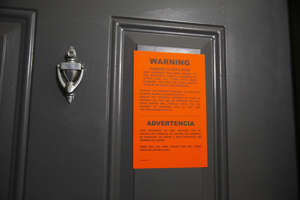 a black sign with white text: An eviction notice is served at an apartment.