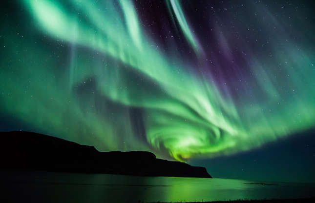 Slide 11 of 41: The Northern Lights, or aurora borealis, is a natural light display occurring between late September and late March. Renowned for their magical appearance, these majestic purple and green bands of light cover a wide geographical area, however, some of the most spectacular shows happen above Iceland, as seen in this image.