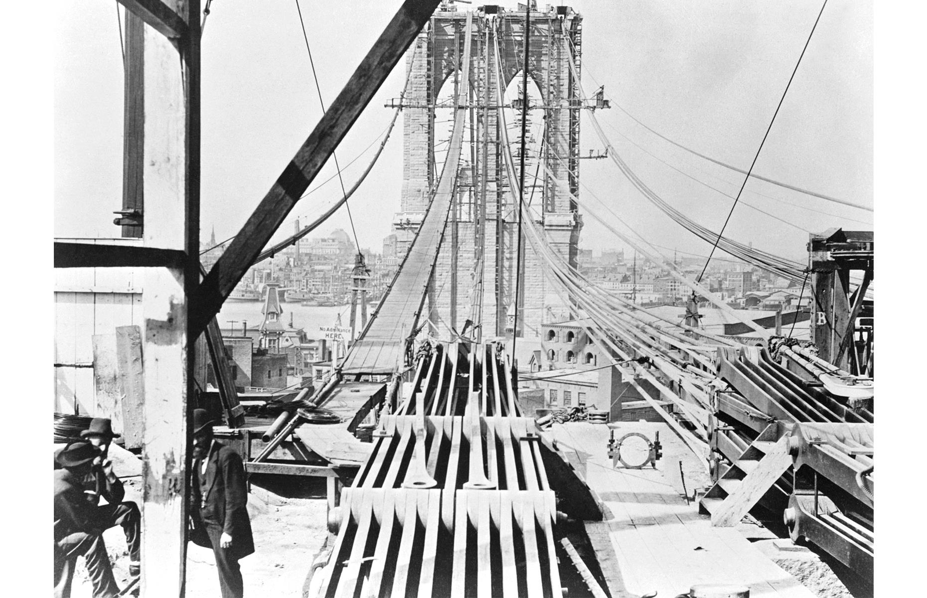 "Slide 12 of 41: Other workers died from falls or injuries and many suffered from decompression sickness or ""the bends"" – a result of pressurized air in the caissons the men worked in. Upon the landmark's completion, in 1883, it was the longest suspension bridge in the world, spanning around 1,600 feet (488m) from tower to tower. But even when the structure was finished, there were still fears over its safety. Circus owner P. T. Barnum famously led 21 elephants over the bridge in 1884 to allay the public's anxieties. It's seen here around a decade earlier, as cables were put into place in 1875."