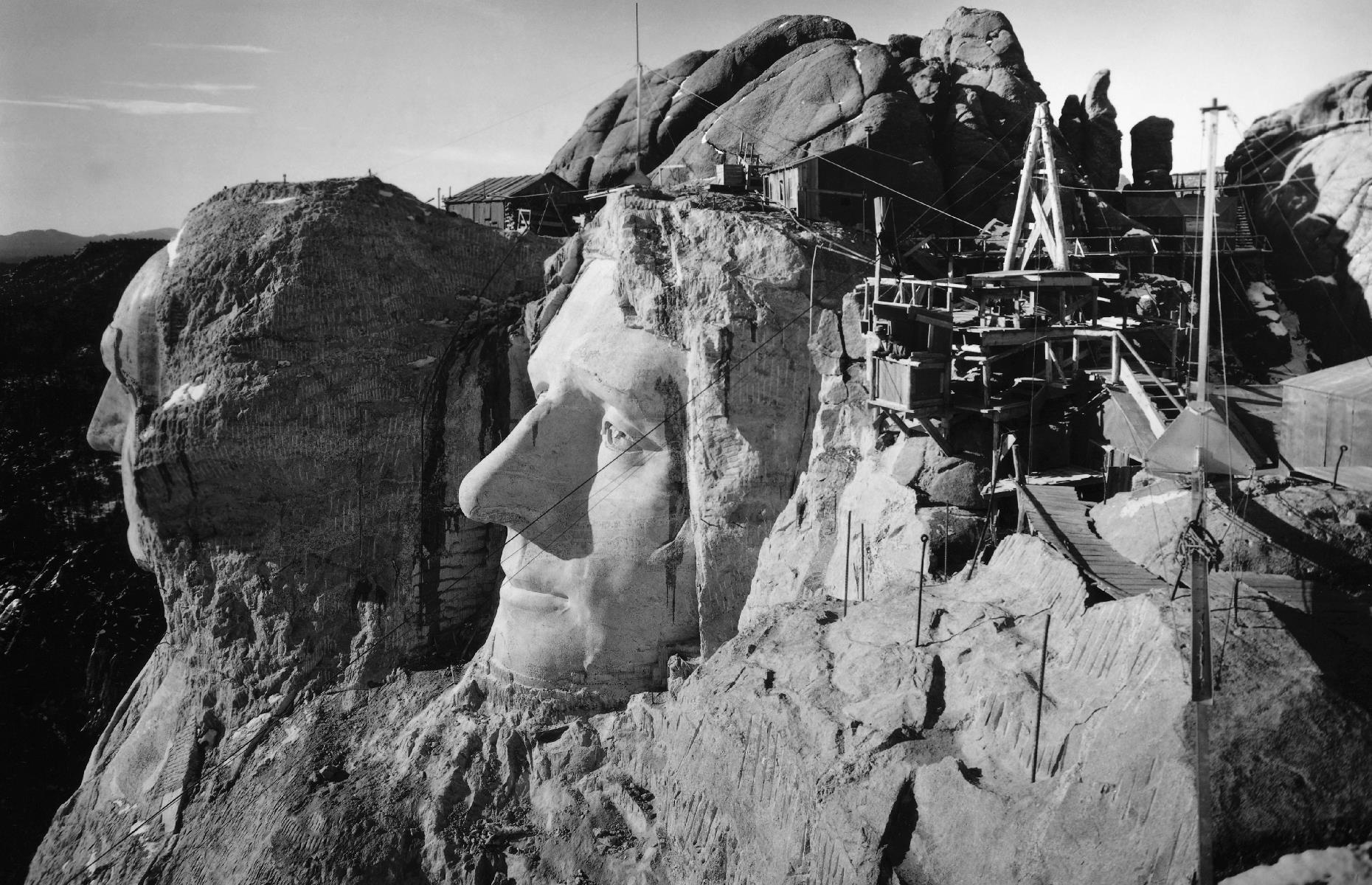Slide 3 of 41: It took around 14 years to build the four, gigantic presidential faces, with work beginning in 1927 and eventually finishing up in 1941. Great chunks of rock were blasted away with explosives, then the striking likenesses were carved out with chisels and jackhammers. This photo was taken circa 1940, towards the end of construction: you can clearly see the sage profiles of Thomas Jefferson and George Washington a little farther away.