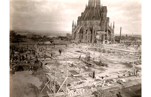 Slide 9 of 41: However, the buildings were ravaged by a fire in early 1916. The Library of Parliament was spared, but the rest of the site, including the Centre Block pictured previously, was gutted by flames. Canada was quick to begin work again, though, and by the end of the year, reconstruction had commenced. This 1916 photograph shows the beginnings of that construction work, with the striking, cupola-topped Library building rising from the foundations.
