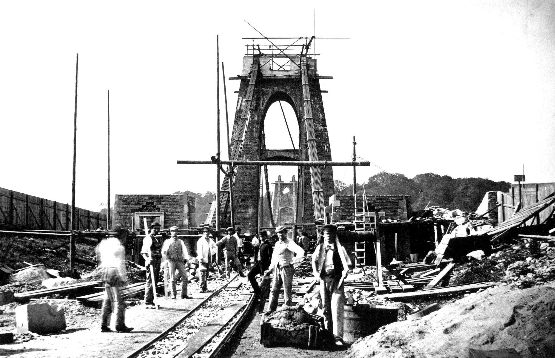 Slide 39 of 41: Work on the bridge – to a design by civil engineer Isambard Kingdom Brunel – wouldn't begin until 1831, after Vick's original bequest had had some time to accumulate. However, the Bristol riots of 1831 soon caused construction to halt and dwindling funds would see that work remained paused for decades. After Brunel died in 1859, the bridge was completed in part as a tribute to the late engineer, with revised designs by William Henry Barlow and Sir John Hawkshaw. It's captured here under construction in 1864, the same year it was finally finished.