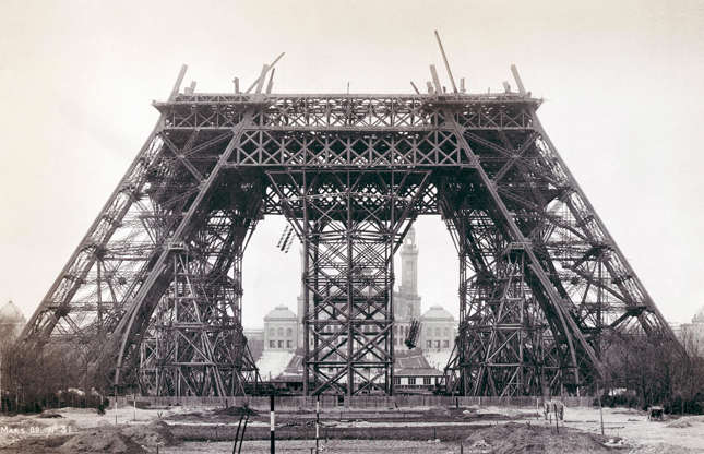 Slide 4 of 41: It took 18,038 metallic parts and some 50 engineers and designers to realize the Eiffel Tower, the great symbol of France that stands proud in Paris. Designed by civil engineer Gustave Eiffel, it was first dreamt up for the World's Fair of 1889, with building work beginning in 1887. You can see the tower beginning to take shape in this photo of the first platform from 1888 – wooden scaffolding (visible here) and small steam cranes were used in its construction.