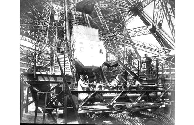 Slide 6 of 41: Upon its completion, the giant latticed tower was more than 984-feet (300m) tall and had taken just 26 months to build. Also a source of fascination was the tower's hydraulic elevator system (seen here under construction), which was a spectacular feat of engineering for the time. Today two historic elevators remain in operation at the tower.