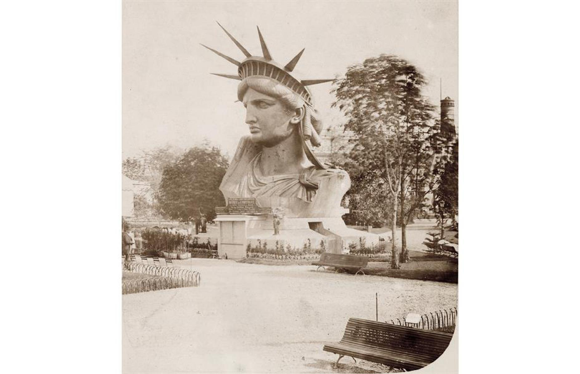 Slide 18 of 41: Before she made it across the pond, though, Lady Liberty was presented in sections at Paris' World's Fair in 1878. This photo shows her gargantuan head propped on a pedestal on display at the event.