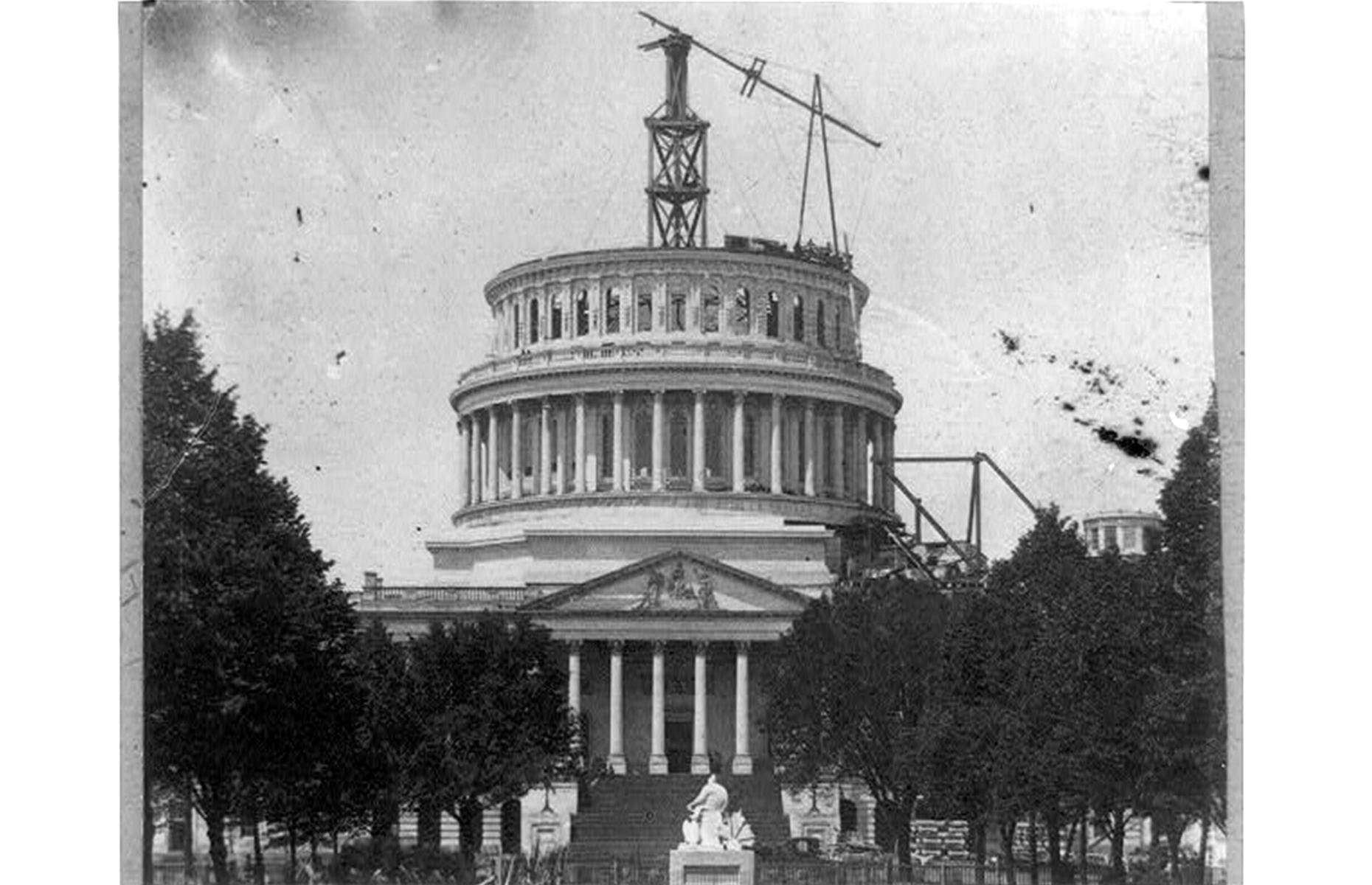 Slide 20 of 41: Though the first wing of the Capitol Building was finished in 1800, the building as we see it today wouldn't take shape until later. The current, cast-iron dome, designed by American architect Thomas Ustick Walter, replaced an earlier one built by Charles Bulfinch in the 1860s. It rises to 287 feet (87m) and was modeled on that of St Peter's Basilica in Vatican City – it's pictured here in 1861 during its construction.