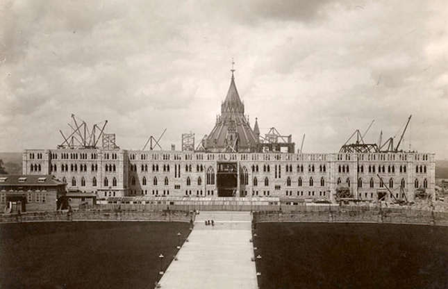 Slide 10 of 41: Fast-forward one year and work continues. This 1917 photo shows Parliament's Centre Block once again taking shape, with the pointed library building peeking out from behind it. The building work, which also included the soaring Peace Tower, was finally finished up in 1927.