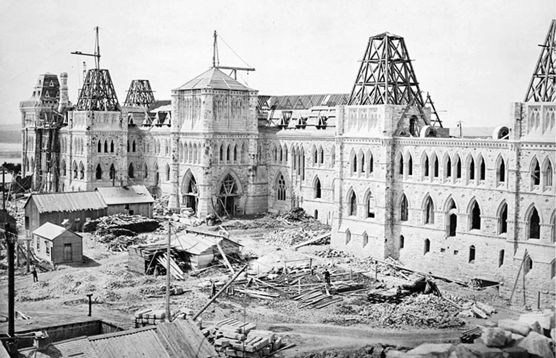 Slide 8 of 41: Canada's Parliament building has had a tumultuous history, beginning right back in the 1850s, when Ottawa was first selected as the capital. Work on the Gothic Revival-style buildings on Parliament Hill began in 1859 and was eventually completed in 1866. The sprawling Centre Block is pictured here under construction in 1863.
