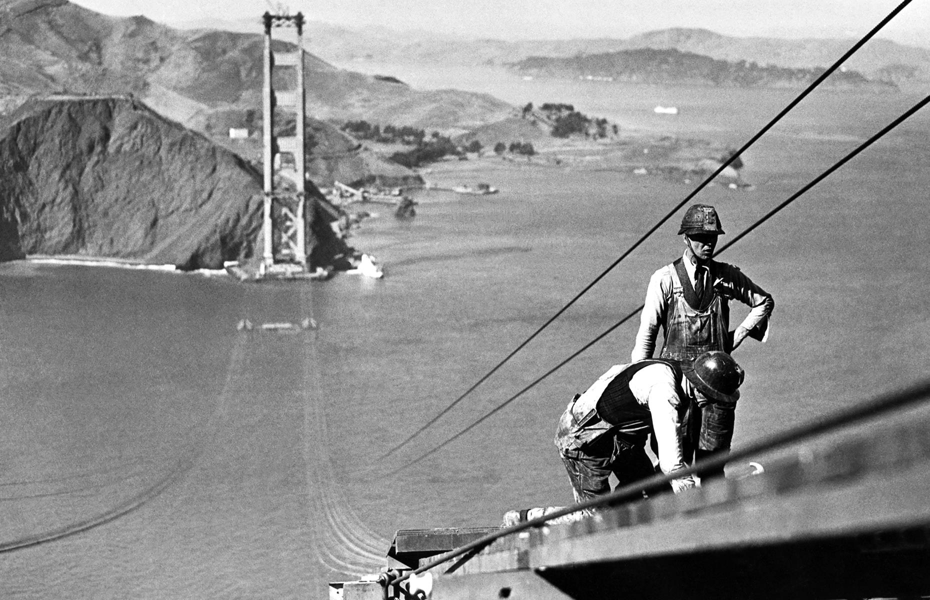 "Slide 40 of 41: When this mighty ""international orange"" structure was first built, it was the longest and tallest suspension bridge in the world. Construction of the bridge, which spans the Golden Gate strait, began in 1933 and proved to be a tumultuous exercise. Eleven people met their deaths during the erection of the landmark, which saw workers brave great heights over swirling currents. Courageous workers are pictured here in 1935, standing on a catwalk as they attach cables from the bridge."