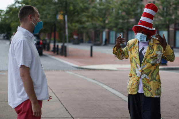 "Slide 25 of 50: Phillip Black, right, wears a face mask to protect himself and others from COVID-19 as he talks with a passerby near Eastern Market on the corner of 7th St. SE and C St. SE, in Washington, Thursday, June 18, 2020. Black is homeless and is a regular on this corner sometimes selling the Street Sense newspaper and asking for donations, often in a ""The Cat in the Hat"" hat."