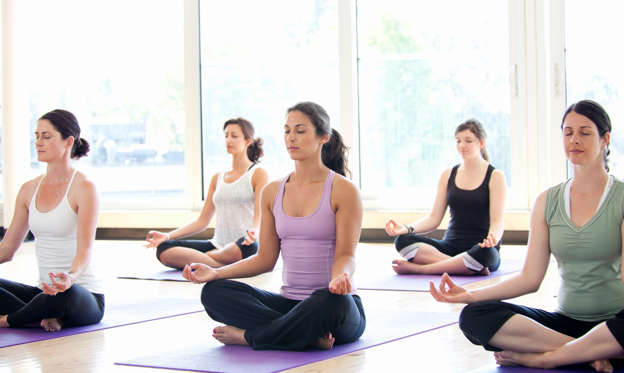 幻灯片 13 - 1: Class of women performing the meditative Sukhasana pose in a bright, modern yoga studio.