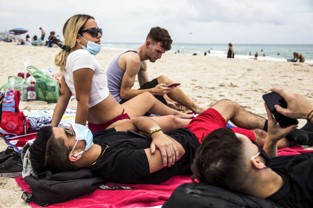 a group of people sitting at a beach: Daniel Milian, from right, Miguel Martinez and Laura De Armas relax at the seaside in South Beach in the city of Miami Beach on June 19. Their group showed a variable approach to wearing masks.