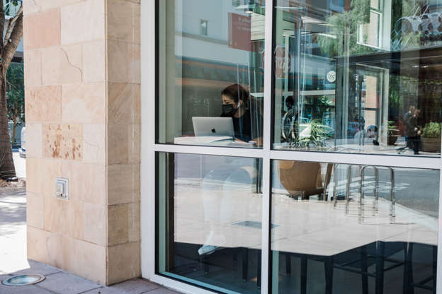 a glass door: A patron wears a mask inside a coffee shop at the Scottsdale Quarter shopping center in Arizona. The state's governor reversed himself and let local leaders adopt their own face-covering policies.