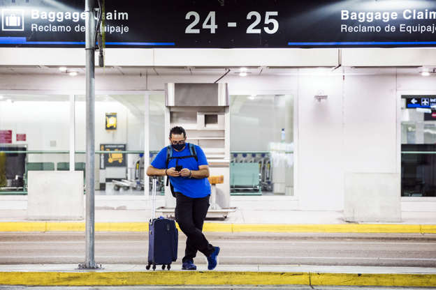 a person standing in front of a building: A traveler waits for a ride June 19 at Miami International Airport.