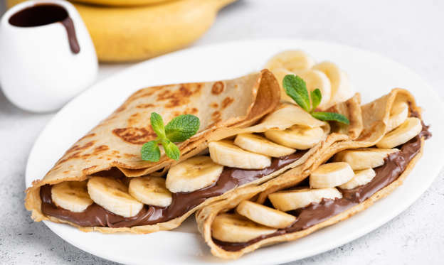 幻灯片 13 - 2: Crepes stuffed with chocolate spread and banana on white plate. Thin pancakes, blini. Sweet dessert.