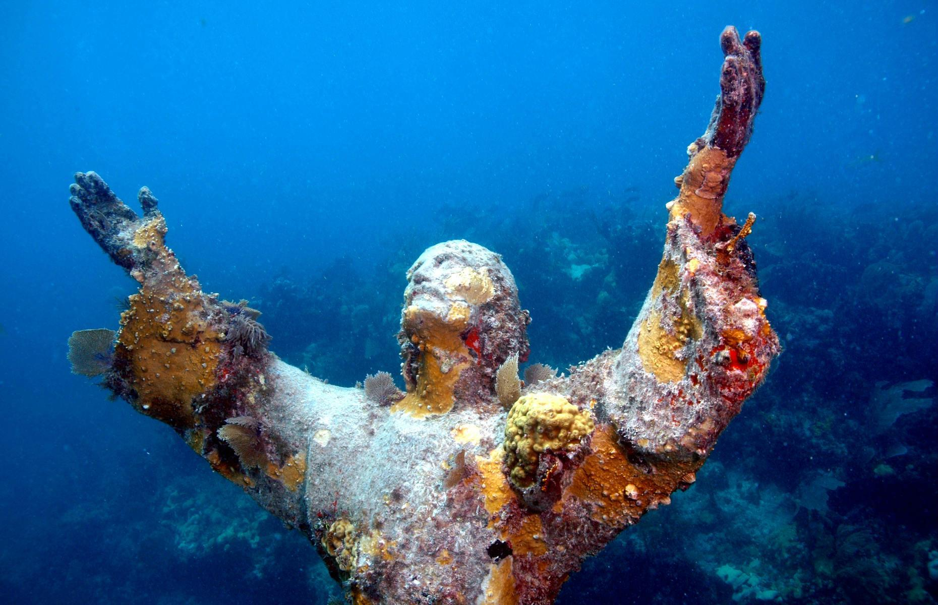 Slide 3 of 31: Set just off Italy's western coast, near San Fruttuoso, this was the original underwater Jesus statue, a figure whose copies can now also be glimpsed in locations around the world. Now coral-encrusted, the statue – arms outstretched, face raised to the heavens – is eight feet tall (2.4m) and set 56 feet (17m) below the water. The sculpture was created by Guido Galletti and commissioned by Italian diver Duilio Marcante in 1954 to honor his friend and fellow diver Dario Gonzatti who died diving a few years prior.