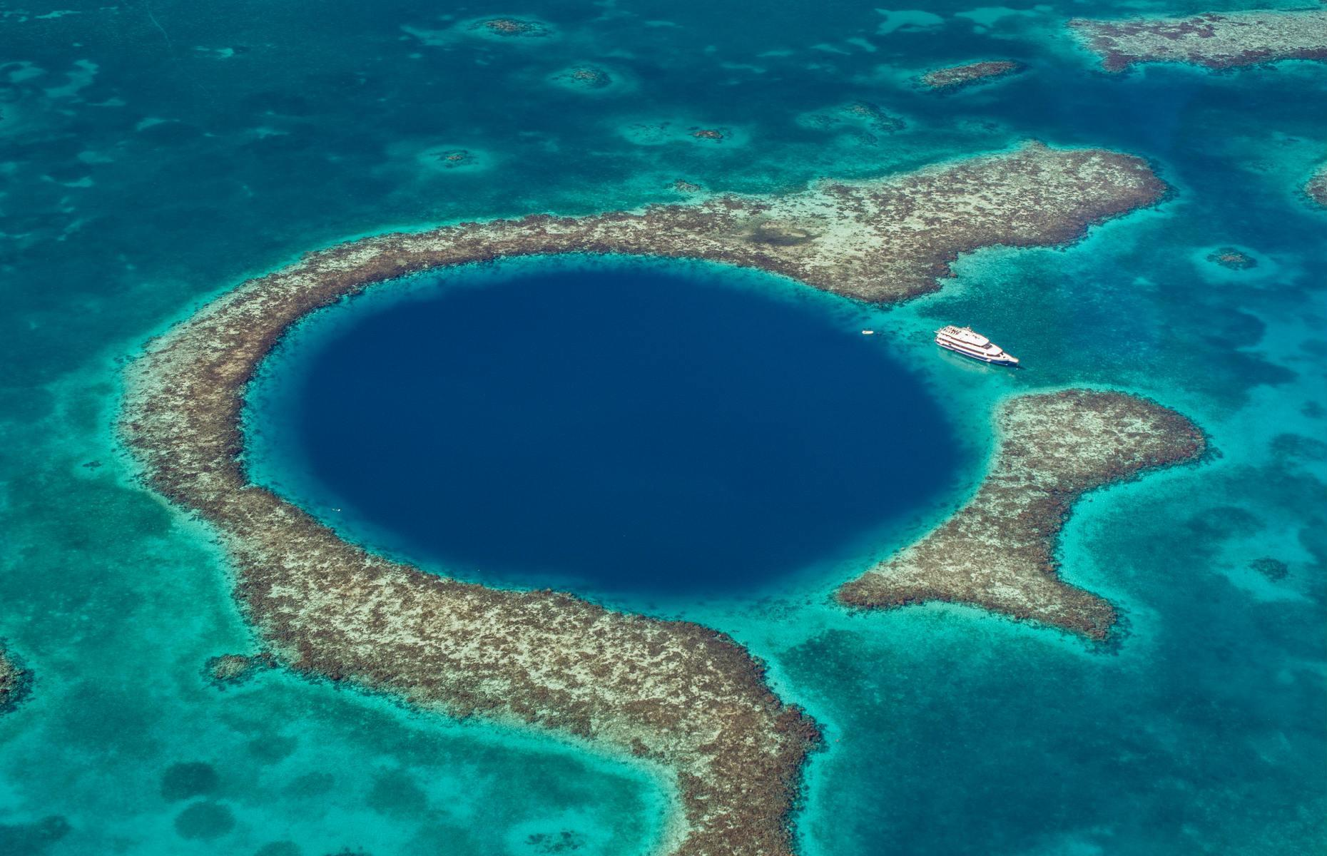 Slide 5 of 31: Set 60 miles from the coast of Belize, surrounded by shallow turquoise waters and encircled by an atoll, this perfectly cylindrical sinkhole blinks from the depths like a vast, inky eye. A dazzling sight from above at 1,000 feet wide (304m) and more than 400 feet deep (122m), this is one of the world's largest submarine sinkholes. It was made famous when the explorer Jacques Cousteau filmed it in the 1970s and today the Belize Barrier Reef, of which The Great Blue Hole is part, is a UNESCO World Heritage Site.