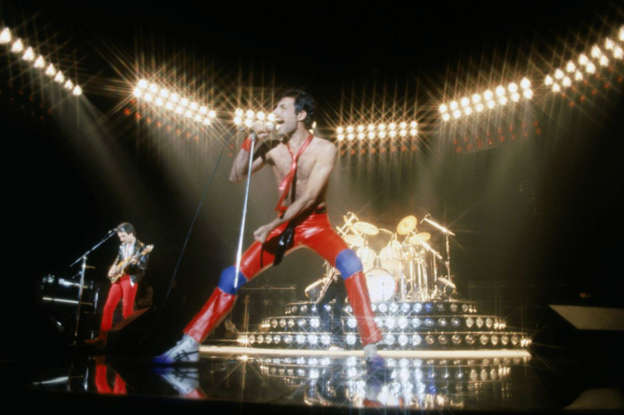 """Slide 3 of 43: This mega-recognizable hit was written after a Queen concert in 1977. """"'We Will Rock You' was a response to a particular phase in Queen's career, when the audience was becoming a bigger part of the show than we were,"""" Brian May explained in an interview. """"So, both Freddie and I thought it would be an interesting experiment to write a song with audience participation specifically in mind."""""""