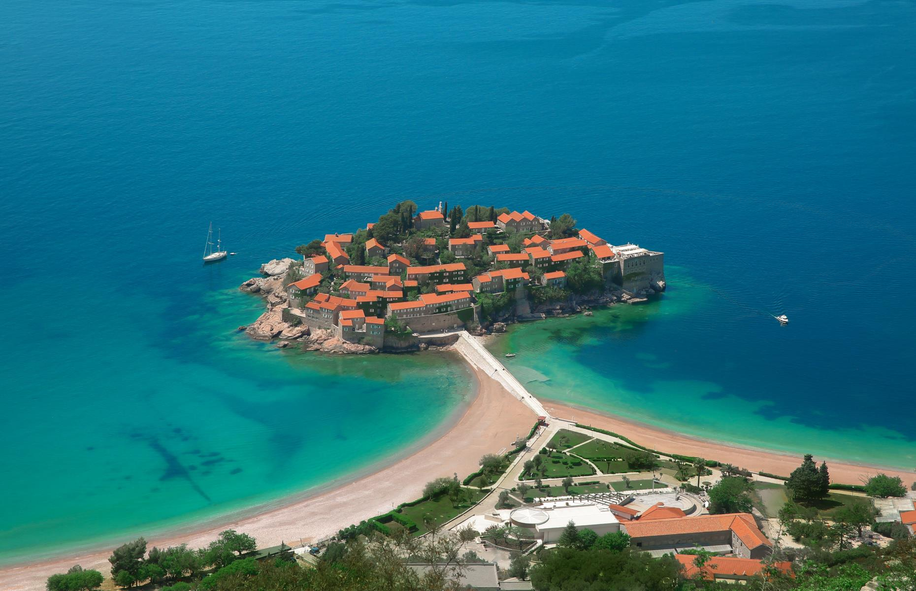 Slide 20 of 31: A small islet off of Montenegro's Adriatic coast, Sveti Stefan is occupied by a ritzy 5-star resort. The public beach on the mainland is this extraordinary site's main attraction, where sunbathers can lie on pink pebble sand and gaze upon the luxurious accommodations.