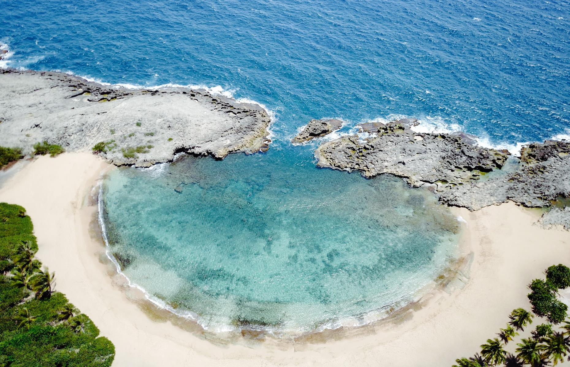 Slide 9 of 31: Few things top the feeling of swimming in a natural ocean pool. The half-moon of turquoise water at Mar Chiquita on the north coast of Puerto Rico is almost fully surrounded by limestone rock, with a small gateway that allows the ocean water to calmly settle in.