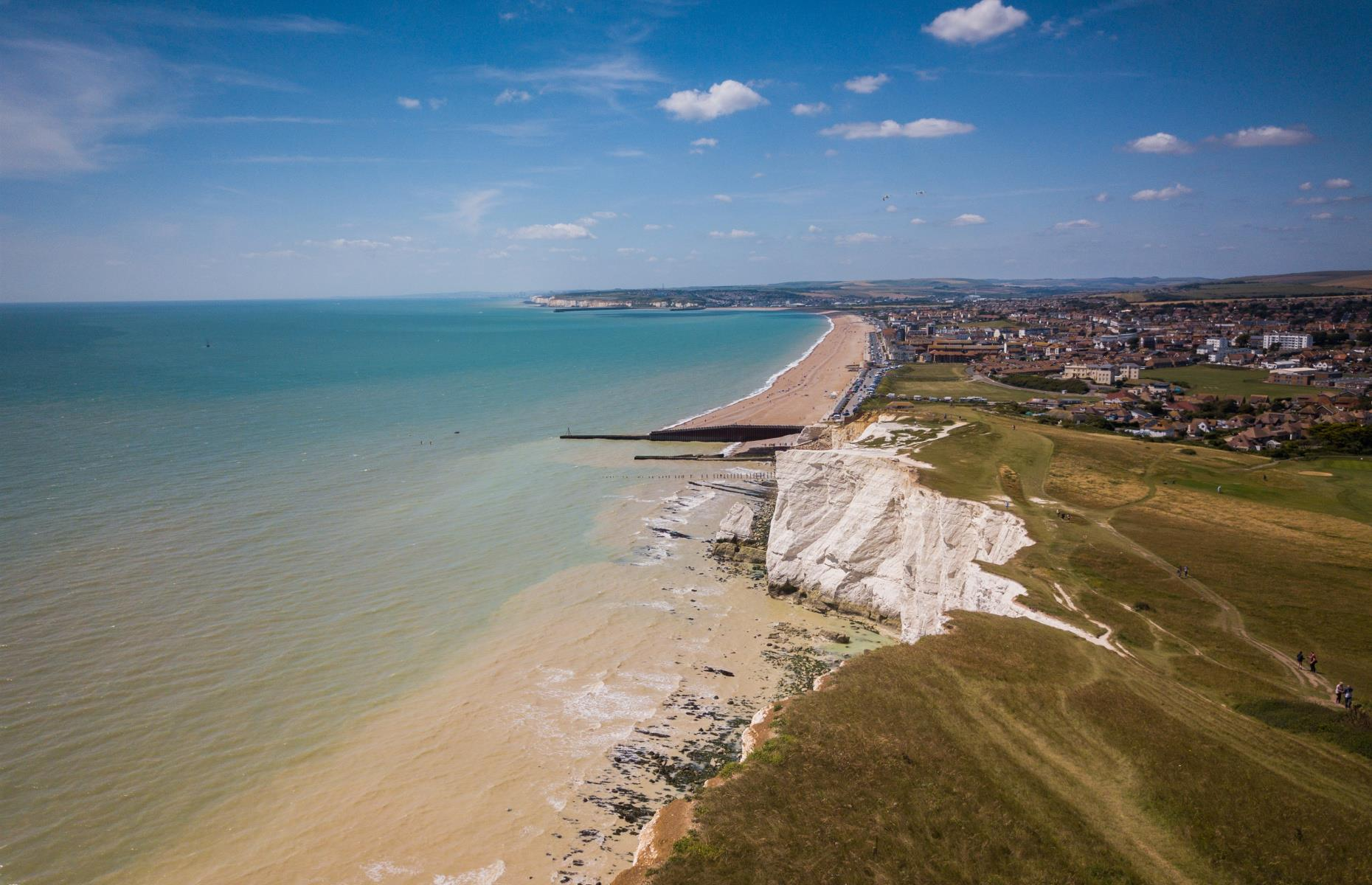 Slide 18 of 31: These chalk cliffs, known as the Seven Sisters, are some of the most famous geographical features of the English seaside. Visitors can enjoy a quiet stroll along the cliffs with easy access to the beach via a walking trail.