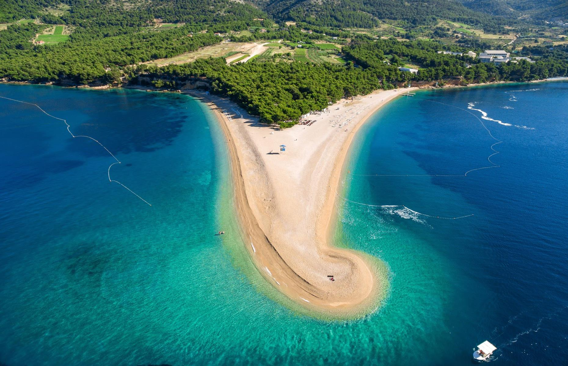 Slide 22 of 31: This arresting triangle-shaped beach is the pride of Brač, one of several Croatian islands in the Adriatic Sea. The beach gets its pointed tip from the accumulation of fine pebbles that have collected on a deep underwater reef. Its position in the sea also makes Zlatni Rat a popular destination for surfers and kite flyers.