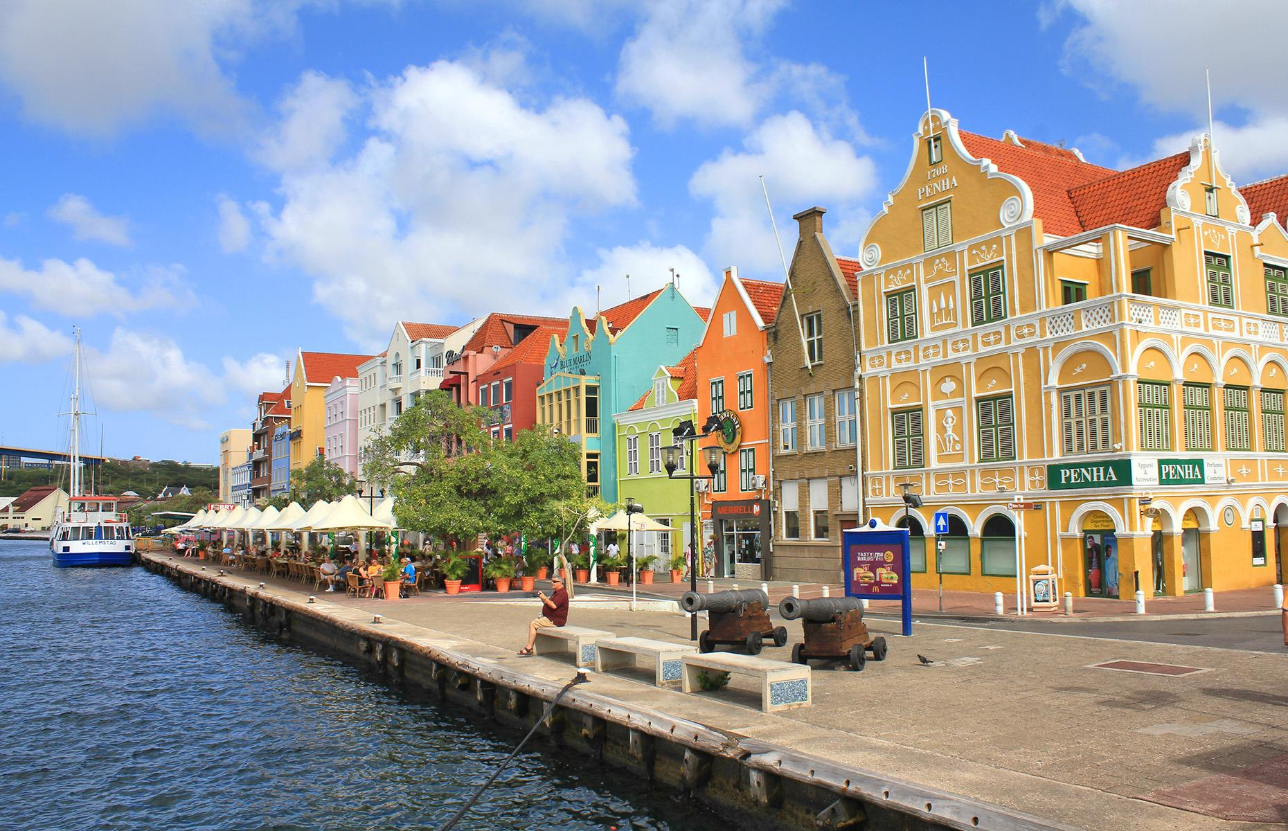 Slide 19 of 51: The history of Willemstad's colored houses sounds like an urban legend, but the buildings in this UNESCO-protected crowd-free Caribbean town were initially painted in an attempt to cure a headache. Back when the Dutch ruled Curaçao, the governor was convinced his migraines were caused by the tropical sun's rays reflecting off the whitewash buildings. All citizens were commanded to paint their homes anything but blinding white, resulting in this rainbow paradise. Take a look at the world's most colorful destinations