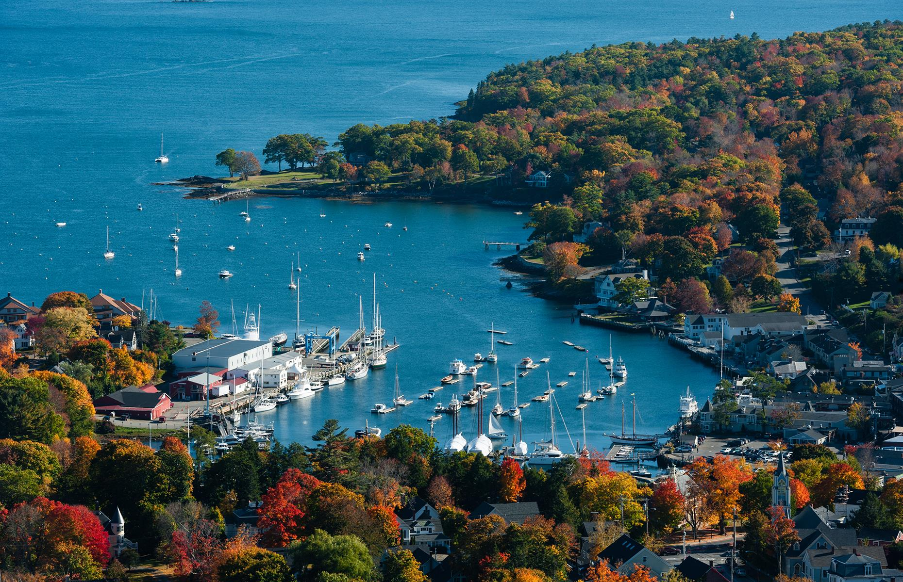 Slide 9 of 51: Nicknamed the Jewel of the Maine coast, Camden is a quintessential seaside town with a charming harbor, an old lighthouse, jagged rock bays and sunset cruises. The nearby Mount Battie showcases gorgeous views over the town, the bay and the surrounding forests.