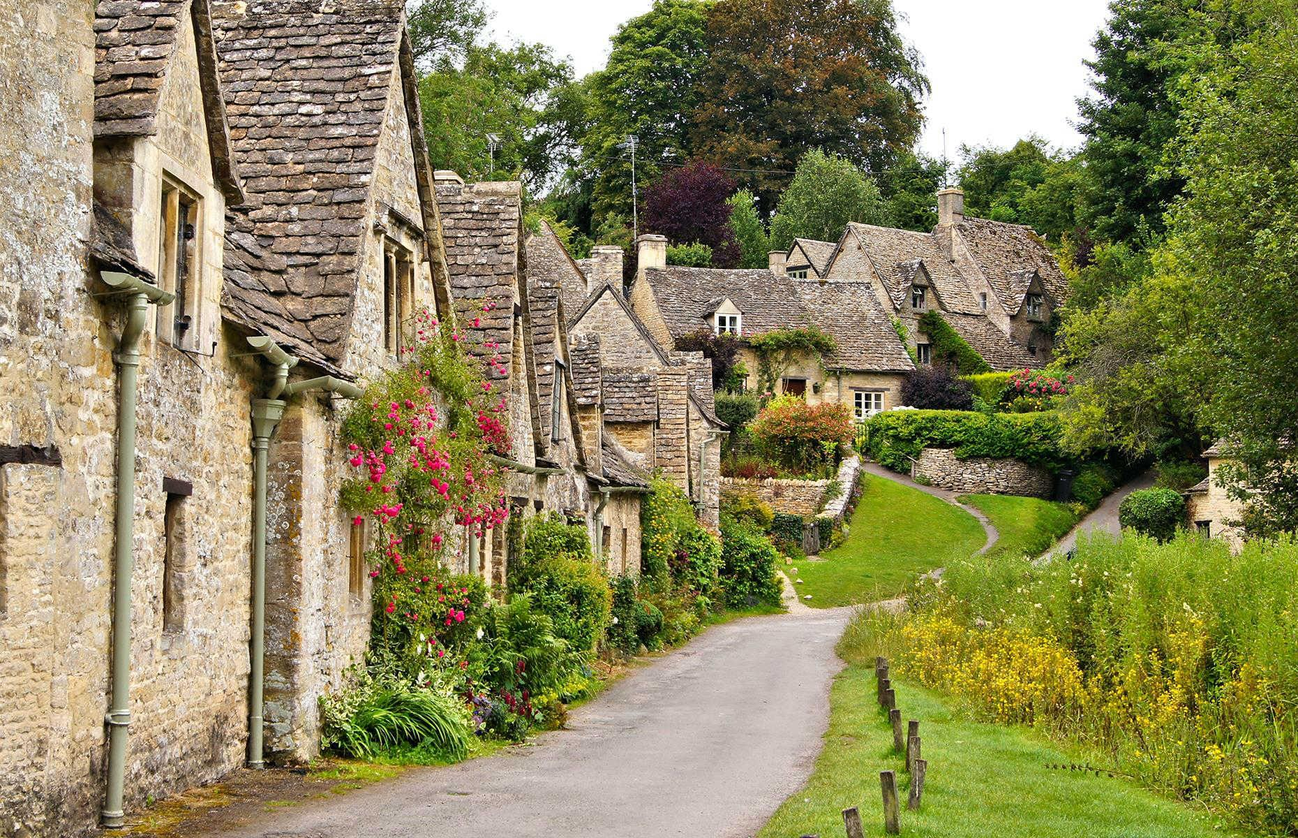 Slide 6 of 51: English writer and designer William Morris once declared Bibury the most beautiful village in the country. A hundred or so years later the sentiment certainly seems to stand. Located in the Cotswolds, an area defined by rolling hills and green meadows, Bibury is picture-perfect. Arlington Row (pictured), a line of weavers' cottages, is the prettiest sight, if not the most famous, in Bibury. Discover more of the UK's prettiest small towns and villages
