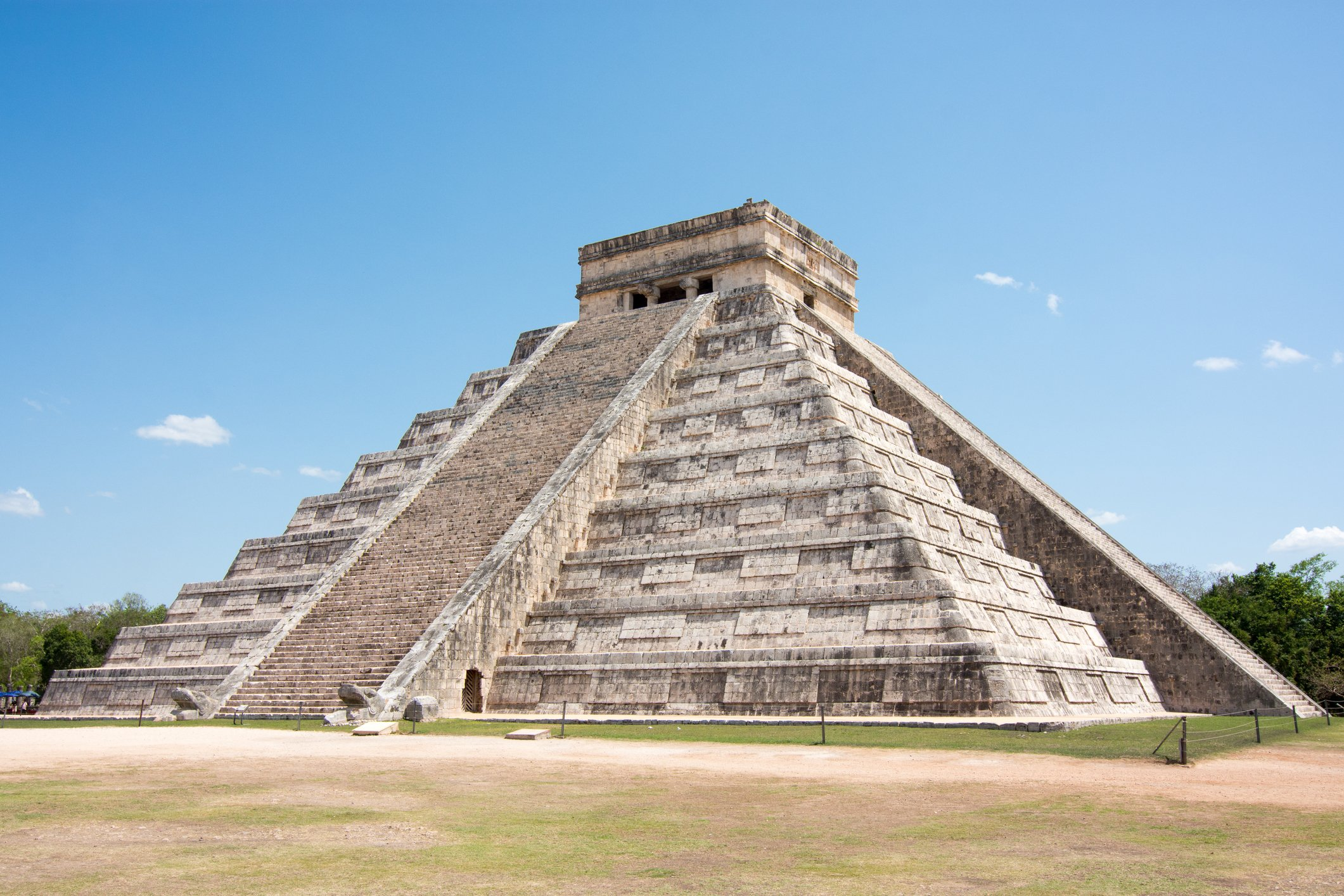 Slide 5 of 8: Though most people may associate pyramids with Egypt, there are some spectacular structures in Mexico as well. One example of that is the Pyramid of Chichen Itza, which is about a two-and-a-half-hour drive from Cancún. Chichen Itza was the ancient capital of the Yucatán Maya, and as a result, it is home to an array of impressive structures, including this pyramid. Built between 800 and 900 CE, the Pyramid of Chichen Itza was designed to be aligned with the summer solstice. Over the course of five hours on the longest day of the year, a combination of light and shadows creates seven triangles on the side of the staircase. And for 45 minutes, it appears as though a serpent is crawling down the side of the temple. The pyramid is dedicated to Kukulcan (or Quetzalcoatl), the feathered serpent god, and according to legend, it was designed so that it appears as though the serpent visits the monument during the summer and winter solstice. Ponder these ancient mysteries researchers still can't explain.