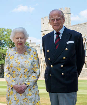 Elizabeth II, Prince Philip, Duke of Edinburgh are posing for a picture: Britain's Queen Elizabeth II and Prince Philip the Duke of Edinburgh pose for a photo June 1, 2020, in the quadrangle of Windsor Castle, in Windsor, England, ahead of his 99th birthday on Wednesday, June 10. The Queen is wearing an Angela Kelly dress with the Cullinan V diamond brooch, while Prince Philip is wearing a Household Division tie.