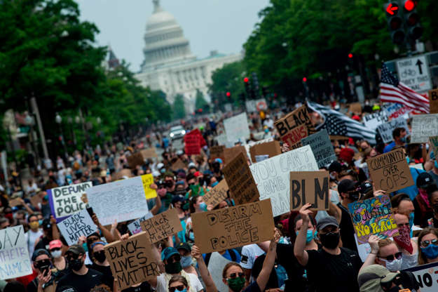 a group of people holding a sign: Protesters walk from the Capitol to the White House during a march against police brutality and racism June 6. Demonstrations have been held across the USA after the death of George Floyd on May 25 while being arrested in Minneapolis.