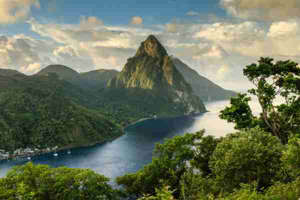 a body of water with a mountain in the background: The Pitons on St. Lucia. (Image by Paul Baggaley / Getty Images)