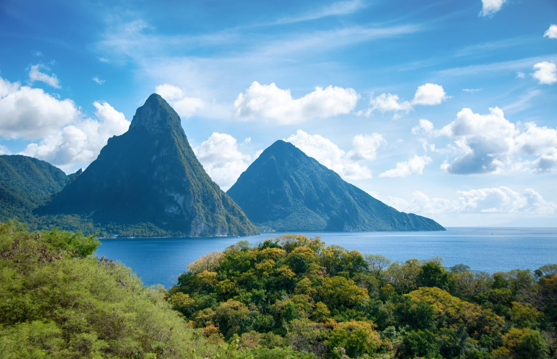 Slide 3 of 31: An unmistakable sight in St Lucia, The Pitons are one of the island's best-known views. The two volcanic plugs are now covered in a dense green jungle and the Pitons – Gros Piton and Petit Piton – are home to no less than 245 different plant species, including eight rare tree species, and 27 bird species, five of them endemic.