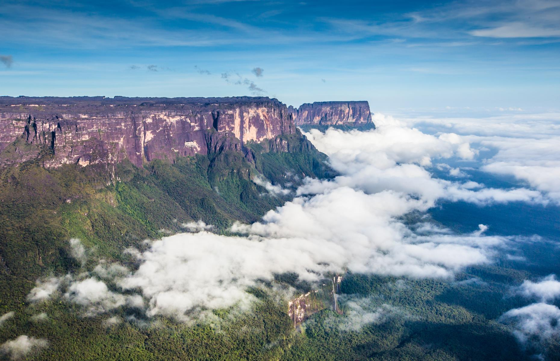 Slide 13 of 31: Towering above the clouds, the majestic Mount Roraima is a natural border between Venezuela, Brazil and Guyana in South America. Around two billion years old, the flat-top mountain is considered to be among the oldest in the world. It's also the highest tepui (South American table-top mountain) on the continent. The otherworldly looking natural wonder is said to be the inspiration behind the plateau with dinosaurs and ape-men in Sir Arthur Conan Doyle's 1912 novel The Lost World.