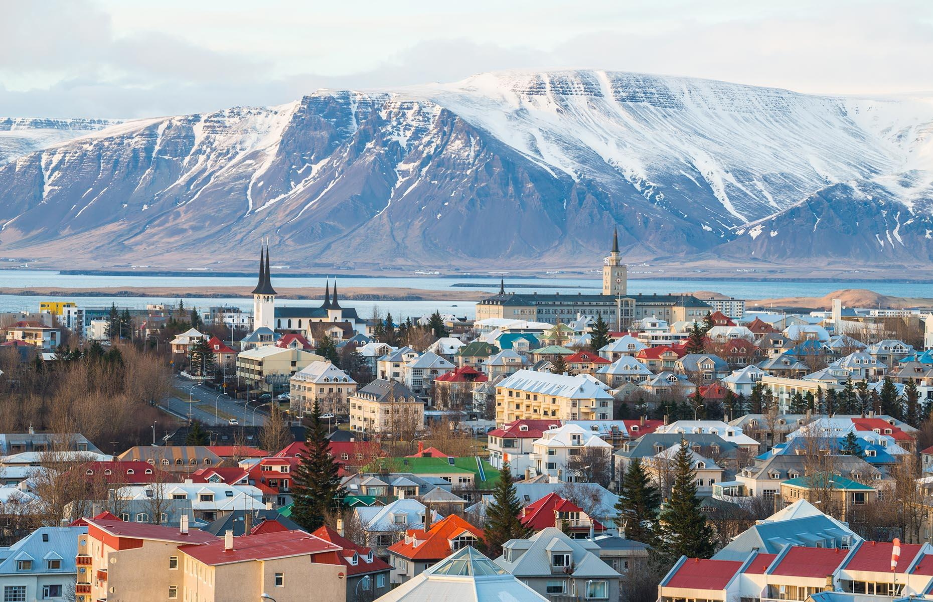 Slide 29 of 41: From its clusters of colorful houses to the sculptural drama of Hallgrímskirkja (a parish church), Reykjavík is one of a kind. Apart from its famous church, most of the city is low-rise, making Mount Esja – usually dusted with snow well into the warmer months – an even more impressive presence across the water.