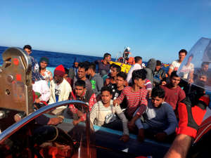 FILE - Migrants react as they are rescued by activists of French NGO SOS Mediterranee boat Ocean Viking off the coast of Libya on June 25, 2020.