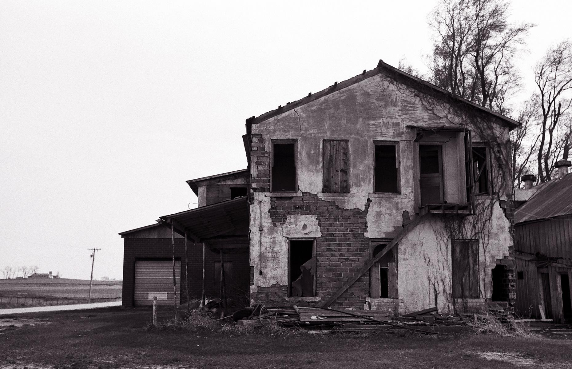 Slide 31 of 101: Today a handful of arresting buildings remain, telling the story of a town that once was. These include a haunting white church, a deserted cemetery and a decaying old creamery building (pictured).