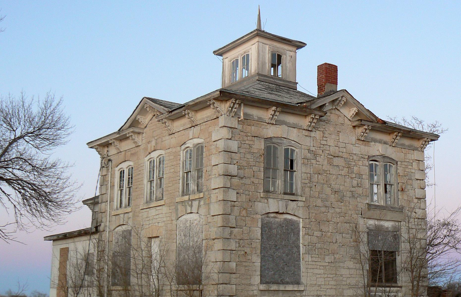Slide 54 of 101: This abandoned house near Ashland dates back to 1874 and is one of the finest examples of Italianate architecture in Nebraska, with its striking cupola, bracketed cornice and hand-chiseled stone.