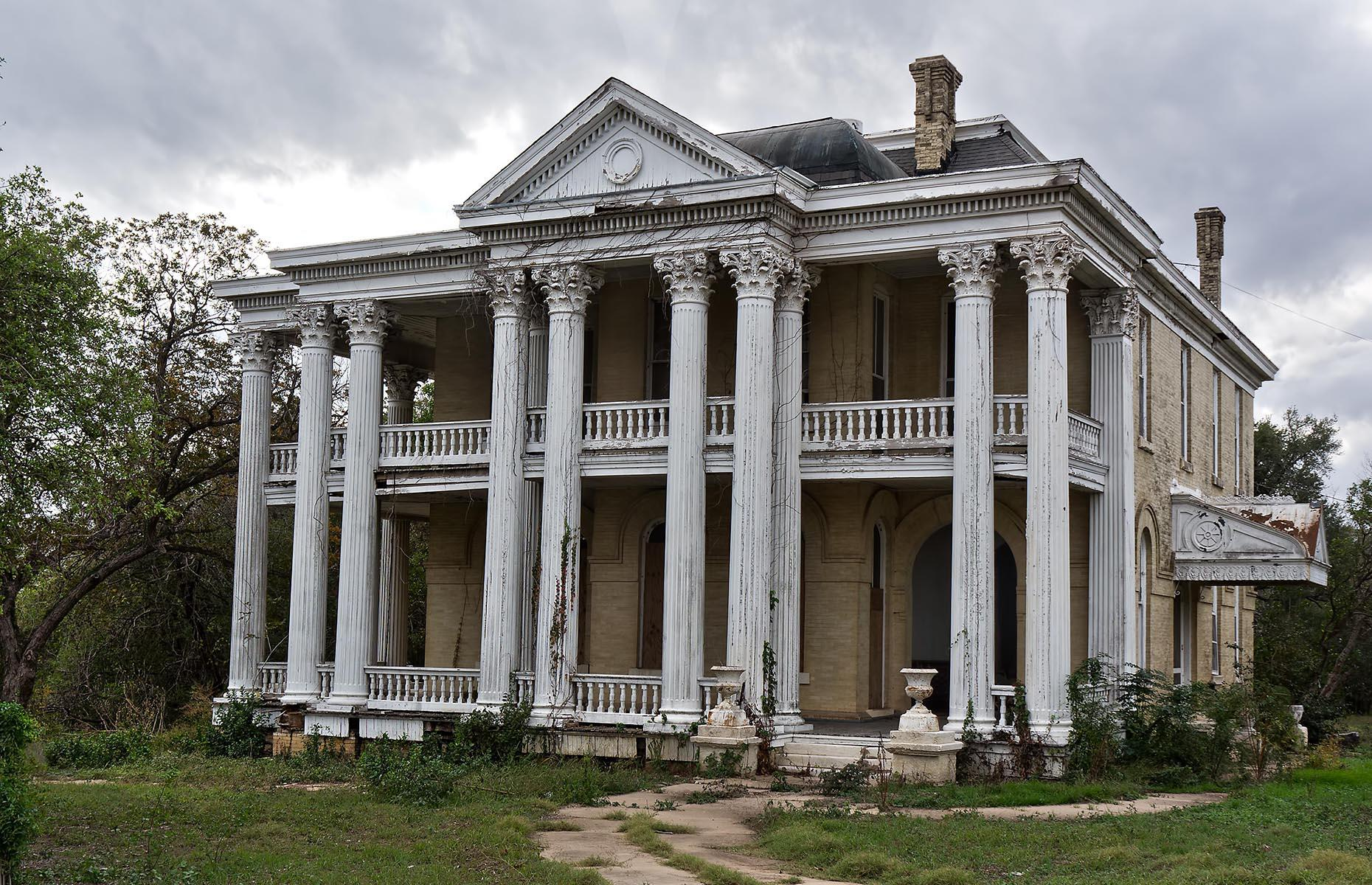 Slide 86 of 101: This elegant Greek Revival-style mansion remains an intriguing mystery. It's located in Gonzales, a small Texan city with a large concentration of stunning historic homes. This one, finished in 1901, was the work of lauded Texas architect James Riely Gordon. It was built for lawyer and politician James Francis Miller, who sadly died soon after its completion.