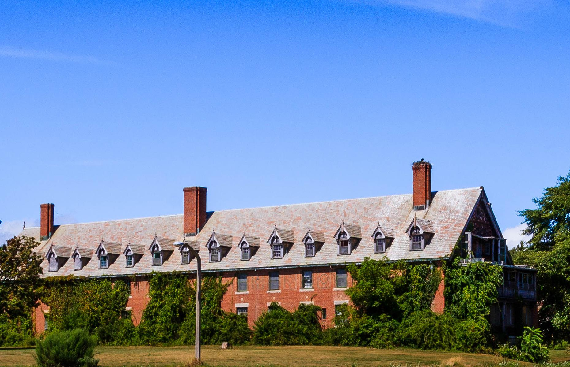 Slide 15 of 101: Today the building still watches over the shore and is within the grounds of the public Seaside State Park. Development plans have circled around the abandoned hospital for years but, as yet, nothing has been decided, so the sanatorium remains eerie and deserted.