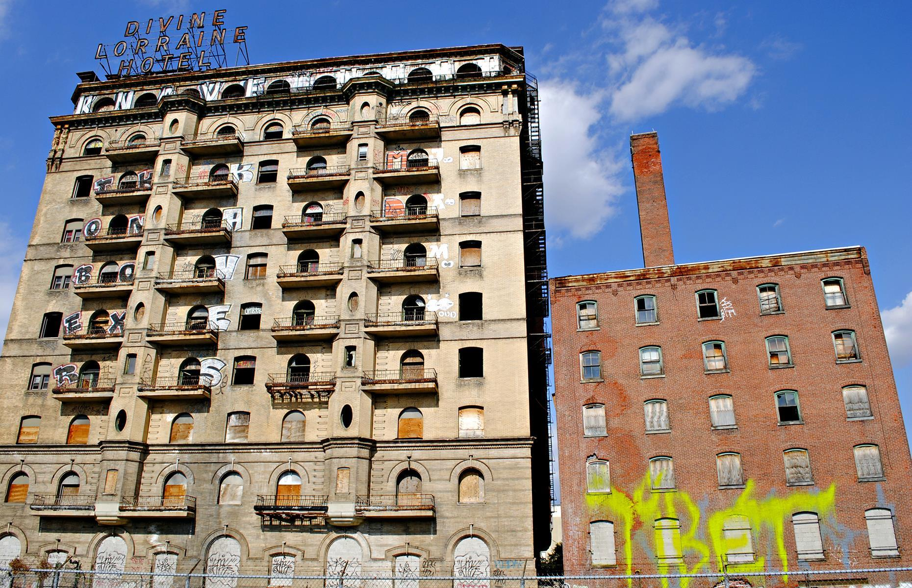 Slide 36 of 70: One of the first high-rise buildings in the city, the Divine Lorraine first served as a luxury apartment complex before it reopened as a hotel in 1900. In 1948 the hotel was bought by spiritual leader Reverend M. J. Divine (or Father Divine, as he was also known), who turned the hotel into the first fully racially integrated hotel in the USA. It closed in 1999 and was reduced to a hollow shell, with no windows, doors or floors remaining. The building has recently been renovated and now houses 101 luxury apartments.