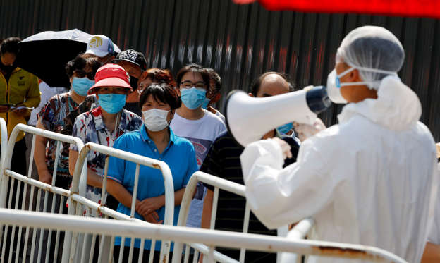 Slide 1 of 50: People line up to receive nucleic acid tests at a temporary testing site after a new outbreak of the coronavirus disease (COVID-19) in Beijing, China June 30, 2020.  REUTERS/Thomas Peter     TPX IMAGES OF THE DAY