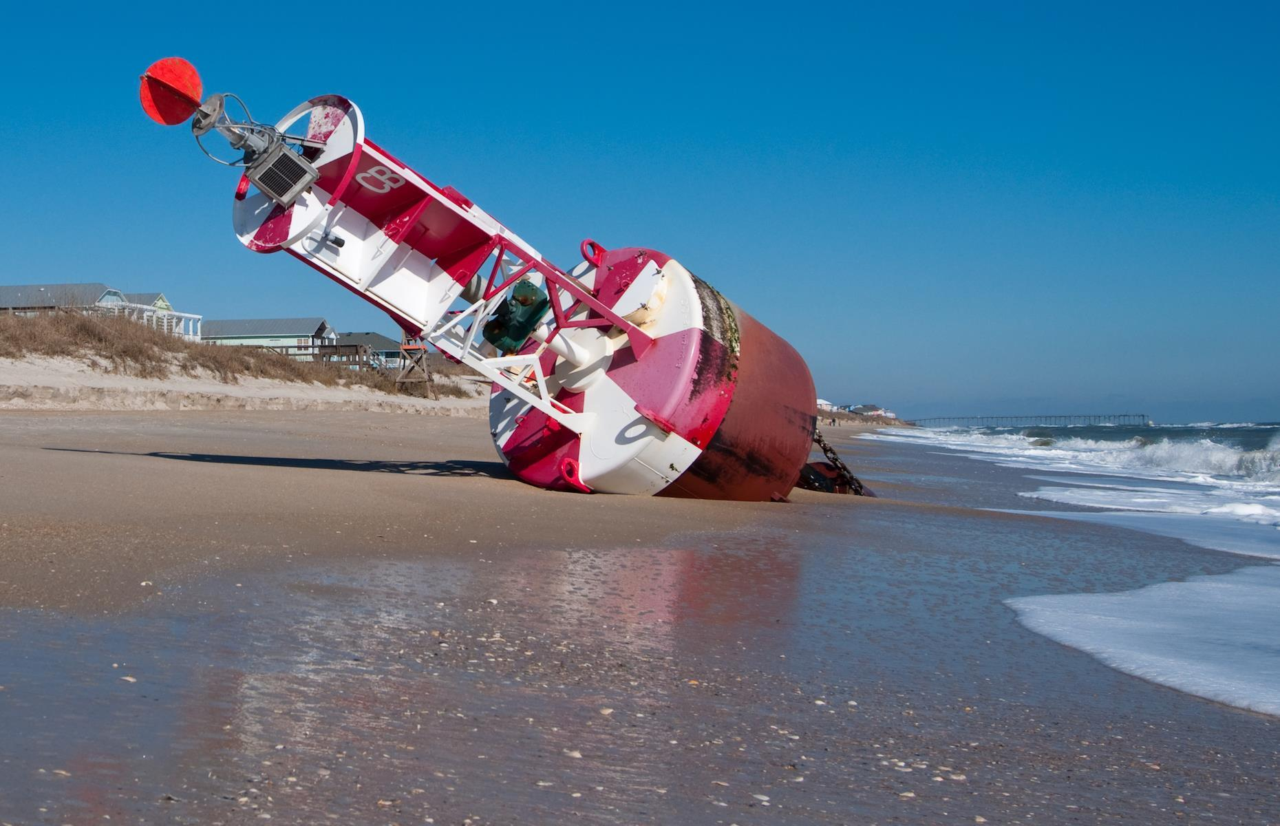 Slide 17 of 33: A large red buoy was spotted lying on its side by walkers on a stretch of shore between South Forest and Coligny beaches in the island of Hilton Head in South Carolina in September 2017. The US Coast Guard buoy was washed ashore during Tropical Storm Irma – it was later identified as Buoy No. 8 and had been carried about eight nautical miles (15km) to the beach by strong waves.
