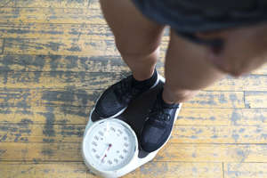 a pair of feet: Low section of man checking weight on scale in gym
