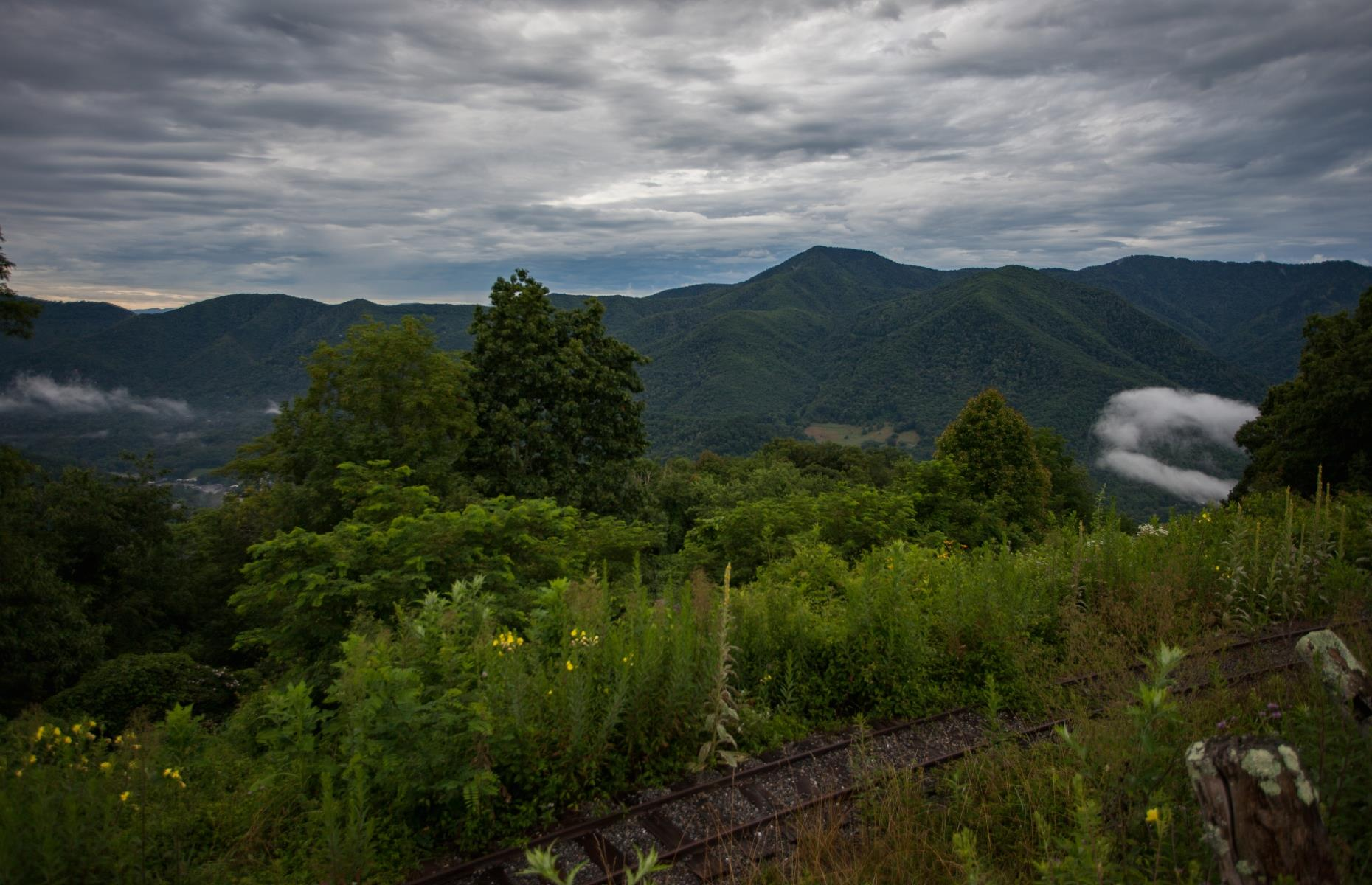 Slide 6 of 28: To visit the park, passengers had to board a double incline railway to the top of Buck Mountain. The exciting journey included multiple slopes towards the peak, varying from 30 to 77 degrees in steepness, and afforded picturesque views overlooking Maggie Valley.