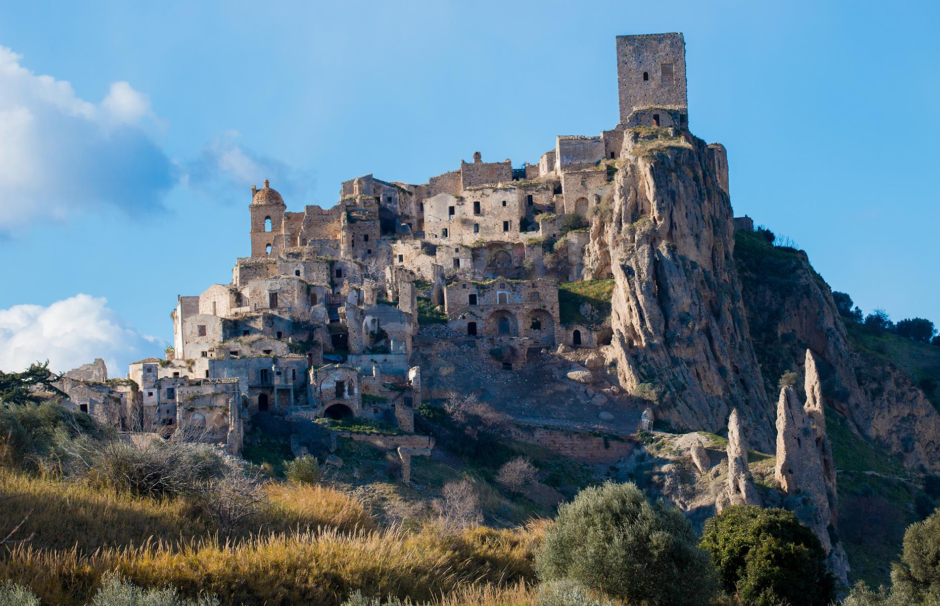 Slide 67 of 68: With a history stretching as far back as BC 540, Craco sits atop a 1,300-foot-high (396m) cliff overlooking the Cavone River valley, at the instep of Italy's boot. After the town was evacuated due to a landslide in 1963, many residents decided not to return. A flood in 1972 worsened the situation and after an earthquake in 1980, the ancient site was abandoned completely.